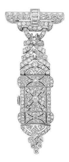 A Belle Epoque Platinum and Diamond Lapel Watch, Circa 1915. Topped by a stylised buckle motif, surmounted by a band of 4 baguette diamonds, joined by flared ribbons, supporting a modified rectangular pierced watch cover centring a floret, opening to reveal a square dial, set throughout with numerous old European single-cut diamonds, with French assay mark, numbered, Swiss movement. #BelleÉpoque #LapelWatch