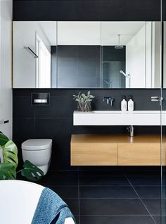 Love the Black Wall and Floor Tile that complements the surrounding White Walls and Bath Fixtures. Alphington Residence by InForm