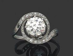 """Bague """"tourbillon"""" en platine sertie d'un diamant de taille ancienne dans un entourage de diamants huit huit. Manque. Poids du diamant: 1.65 cts env. Tour de doigt: 54 Poids brut: 4.95gr A diamond and… - Aguttes - 24/06/2015"""