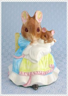 """•Darling Beatrix Potter Musical Figurine •Hunca Munca, or Mrs. Mouse, and her baby •from the children's book """"The Tale of Two Bad Mice"""" •it plays """"Rock-a-bye Baby"""" lullaby •Large porcelain figure •Pastel blue, yellow and pink •Perfect for nursery decor or as a gift for a new mother"""