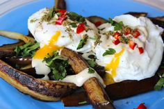 Two garlic poached eggs on a pile of fried eggplant slices drizzled with tahina sauce with some za'atar, fresh parsley and red chilli thrown on top.