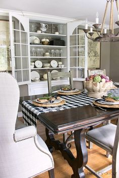 Dining room china cabinet decorated for fall with white pumpkins