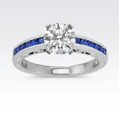 Color is the name of the game with this gorgeous vintage inspired ring. Twelve round channel-set sapphires, at approximately .33 carat total gem weight, will provide the perfect backdrop to the center stone of your choice.  Crafted in quality 14 karat white gold, the milgrain detailing and side engraving adds pizzazz.