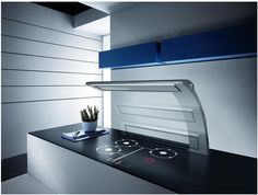 The high tech rising motion of Elica's Eagle reveals its beguiling aerodynamic shape and shows the supporting arm, which enhances suction directly from the hob thanks to its curved position.