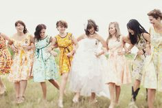 A happy crew of bridesmaids in flowered dresses.