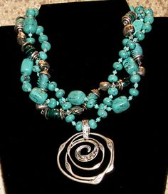 Two Premier necklaces, Cabo and Sweet Waters, twisted together with a removable magnetic pendent, silver swirl.