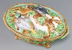 """Lot 20, A Victorian Minton Majolica oval game pie dish and cover, the lid decorated with a hare, swallow and blackbird, the basket weave base with acorn decoration and twin handles. Pattern 899, 13""""w, est £100-200"""