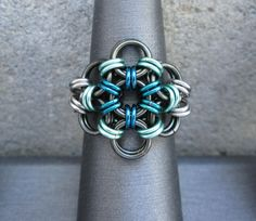 I made this chainmaille ring with teal green, sea foam green, and dark gunmetal enameled copper jump rings. The silver colored rings are stainless