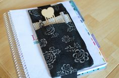This deluxe pen holder band is the perfect solution for holding your pens in style and easily doubles as a place holder or bookmark! This pen holder features two front pockets for holding pens, pencils, and more, as well as a zipper pouch for easily storing your cell phone, keys, money, license or anything else you can think of! The main fabric is a Black floral pattern, and the accent fabric is a soft polka dot. The elastic is heavy-weight knit making it durable and capable of holding…