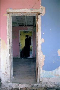 Dilapitated pink, blue and yellow building.  Woman in a black dress.