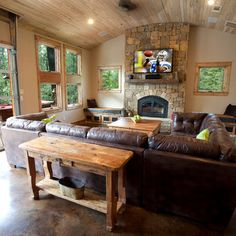 family room inspiration:  acid stained concrete floor large windows/lots of natural light stone fireplace w/bench seating on either side wood plank ceiling/recessed lighting leather sofa sectional