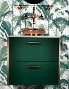 Un meuble-vasque vert bouteille et un papier peint à motifs feuillage. Invitation au voyage garantie !
