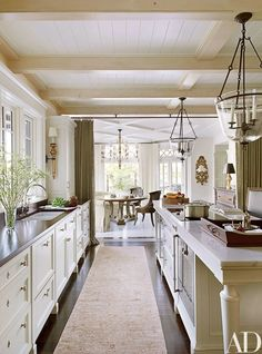 Lanterns by Formations are suspended in the main kitchen, which has cabinetry painted in a Benjamin Moore off-white, a Rohl sink with Lefroy Brooks fittings, and a Gaggenau cooktop and oven | archdigest.com