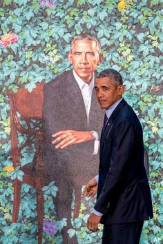 PRESIDENTIAL POSE: Former President Barack Obama, above, walks past his official portrait yesterday at the Smithsonian's National Portrait Gallery. At right is a portrait of former first lady Michelle Obama.