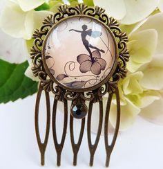 Dieser kleine Haarkamm besteht aus bronzefarbenem Metall und einer filigranen Fassung. Der handgearbeitete Glas-Cabochon zeigt ein wunderschönes Elfen