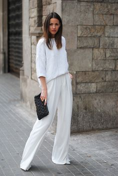 Black clutch, monochromatic embroidered white three quarter sleeve shirt, flowy white pants