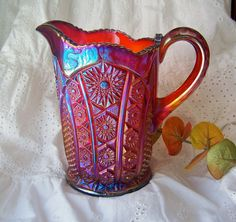 Indiana Red Heirloom Carnival Glass Pitcher.   Beautiful iridescent sunset pattern pitcher picks up the light of its surroundings.  Vibrant red Carnival Glass pitcher is in Mint condition.  Pitcher measures 7 1/4 inches tall by 7 inches from lip to handle.  Carnival glass Pitcher is very heavy, weighs 3 pounds.1975-1976*$69