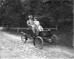 Ladies out for a Sunday Drive! View of Mrs. A. H. Sanborn and Mrs. Jennie Hackett Farnham in an Early Electric Automobile on an unknown dirt road. View taken in Stark Park.  Credit Manchester Historic Association
