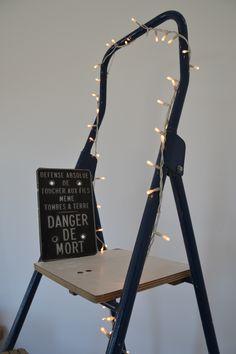 """Trouvailles de brocantes - panneau emaillé """"Danger"""", escabeau vintage et guirlande lumineuse."""