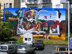 A colorful mural in San Francisco, featuring Chaim Potok's The Chosen, Gabriel Garcia Marquez's 100 Years of Solitude, Maya Angelou's I Know Why the Caged Bird Sings, The Art Book, Cervantes's Don Quixote, J.D. Salinger's Catcher in the Rye, and Douglas Adams's Hitchhiker's Guide to the Galaxy. [Photo via]