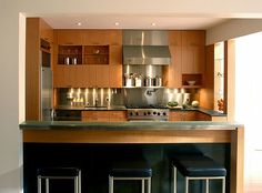 Wood and stainless steel decoration for a modern looking kitchen    Interesting how this kitchen furniture covers a full wall, actually making it an accent wooden wall for the entire area - by Cary Bernstein Architect
