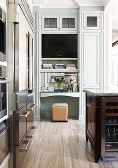 MY DREAM KITCHEN!!!! Limestone Floors;lightest shade of mint green for walls/cabinetry/trimwork;desk alcove w/ mirrored back, cookbook storage & TV;ceiling height cabinets & crown molding add height to space;top cabinets w/ dark glass windowpane fronts hide things & keep eye moving up w/o becoming too cluttered; high & wide arched opening adds architectural detail & lets natural light in;stainless steel;island w/ built in wine cooler @ end... STUNNING!!!!