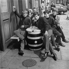 A photo when the Rolling Stones were starting out in the year Mick Jagger and the gang are having fun with their beers outside the pub.
