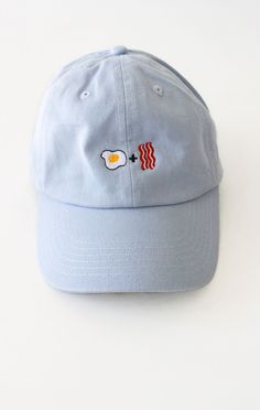 - Description Details: Six panel cap in light blue with 'Egg + Bacon' embroidery…