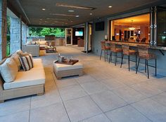 "The covered patio, connected to the home via folding doors and windows, features a bar, an outdoor kitchen and inviting seating areas. This is the way to do an ""outdoor room"". Indoor Outdoor Living, Outdoor Rooms, Outdoor Furniture Sets, Outdoor Bars, Outdoor Kitchens, Indoor Balcony, Balcony Garden, Outdoor Patio Bar, Adirondack Furniture"