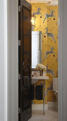 I know the Scalamandre Zebras are way overexposed right now, but this combination of the yellow colorway, lovely creamy marble floors and sink, hint of a polished nickel lantern, and that absolutely fabulous black gloss door with a circular moulding detail is really working in this glamorous powder room.