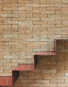 Impossível não notar a parede revestida de tijolos no tom palha (22 x 11 cm, da Olaria Spina), assentados com junta seca – argamassa não aparente. Desenho da arquiteta, a escada metálica é outra atração. As chapas de ferro (3 mm) dos degraus chegaram dobradas da Serralheria Evolução e foram soldadas entre si na obra. Depois, bastou prender o conjunto no piso e encaixá-lo em cortes nos tijolos. Cabos de aço descem da viga e transpassam o metal, completando a sustentação.