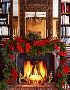 Bronson van Wyck - Architectural Digest This fireplace mantel is decorated with a cedar garland and red Chinese paper fans.