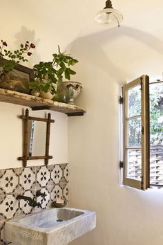 look at the tiles in front of the sink, and the little mirror, the wooden rack on the top with plants and stuff, even the light is awesome. The open window makes it perfect!