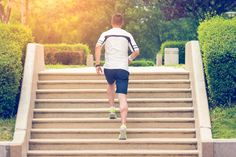 Muscular sportsman running up on stairs. Morning workout. Urban