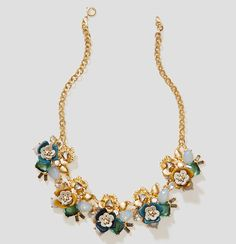 This statement necklace bursts into bloom with gleaming metallic, dreamy color and glowing stones. Goldtone finish. Spring ring clasp.