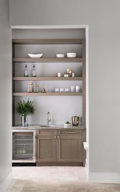 Gray wash wood floating shelves are stacked above gray wash cabinets in a butler's pantry boasting a glass front beverage fridge and a round sink with a satin nickel gooseneck faucet fixed to a gray granite countertop.