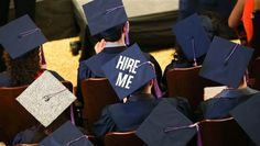 A student from the Syracuse University School of Architecture wears the words 'HIRE ME' on his graduation cap during the commencement ceremo...