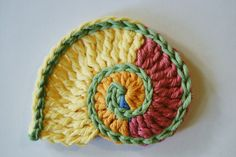 The nautilus shell is a popular motif in freeform crochet. It's made in the same way as the spiral, or two-colored spiral, except the height of the stitches progressively gets higher, creating a wi…