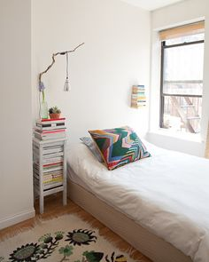 A DIY branch lamp, neatly stacked books and colorful pillow add personality to this small sleeping area.