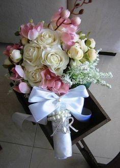 Lindo bouquet de rosas na cor champagne de silicone ao qual imitam perfeitamente o toque,aparência e textura de uma rosa natural, juntamente com camélias, 1 haste de orquídea cor rosa, e envolto de galhos brancos de erva-doce tudo em silicone!  O bouquet é composto por aproxim. 40 flores entre tamnho P e M, e no laço acompanha pulseir de pérolas(initação) e STRASS + iniciais dos noivos em STRASS  É um bouquet eterno de uma recordação infinita.