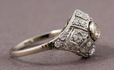 Bague platine 1920, motif central pavé de diamants taille rose avec un diamant central de 0,10 carat. PIERRE BARBOZA