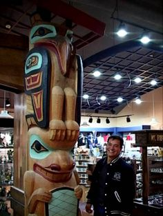 Artist Doug Chilton stands next to his totem pole Raven Beaver    For more information about totem poles, visit: http://www.totem-pole.net/