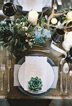 rustic wood table set with eucalyptus leaves, wax flowers, succulents and ivory pillar candles