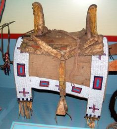 Plains women favored the Spanish war-saddle style, used in this Arapaho HIGH-BOWED SADDLE. The owner would add an ornate SADDLE BLANKET for special occasions. A rawhide QUIRT, or whip, hangs from the saddle.