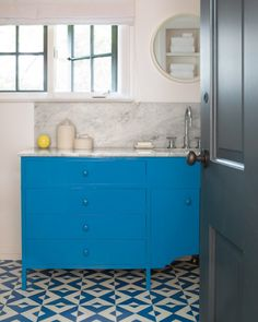 """In the second-floor bathroom, Bestor had a vanity custom-made to incorporate details from the rest of the home's cabinetry, and then she modernized it with cornflower-blue paint. """"In older houses, I like to use traditional details but recontextualize them,"""" she says. Plus, """"I like how this cabinet echoes the color pop from the floor.""""Porcelain rope canisters, from $84, hausinterior.com. Cool Coblat paint, by Glidden, homedepot.com."""