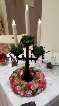 Chandelier agrémenté d'une couronne de fleurs.