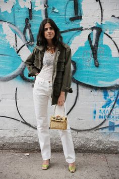 Summer street style fashion: Leandra Medine in khaki utility jacket over white lace top + white jeans pants + raffia handbag + lime green sandals.