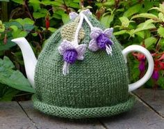 Fuchsias are one of my favourite flowers and I have made a pretty tea cosy with these flowers attached. There are two fuchsias on the front and one on the back and they are crocheted using purple and lilac cotton. There is a green knitted leaf on the . Tea Cosy Knitting Pattern, Tea Cosy Pattern, Knitting Patterns Free, Scarf Patterns, Free Knitting, Crochet Cozy, Crochet Yarn, Crochet Granny, Hand Crochet