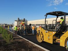 The vibratory roller begins making its passes on a fresh mat of asphalt in a paving operation at a warehouse complex in West Sacramento, Calif.