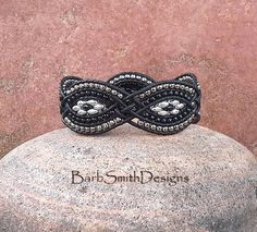 The Twisted Sister - (The Petite One in Black)  Shes back by popular demand, all glammed up in black! What makes this petite sister twisted is the leather weaves that give this cuff her shape! This unique 5-row beaded leather bracelet features four (4) sections of silver and black Super Duo beads, surrounded by silver-toned Toho and black seed beads. It is stitched on natural dye black leather cord. The closure is a silver-toned 5/8 Bali button surrounded by a button loop of silver-toned…